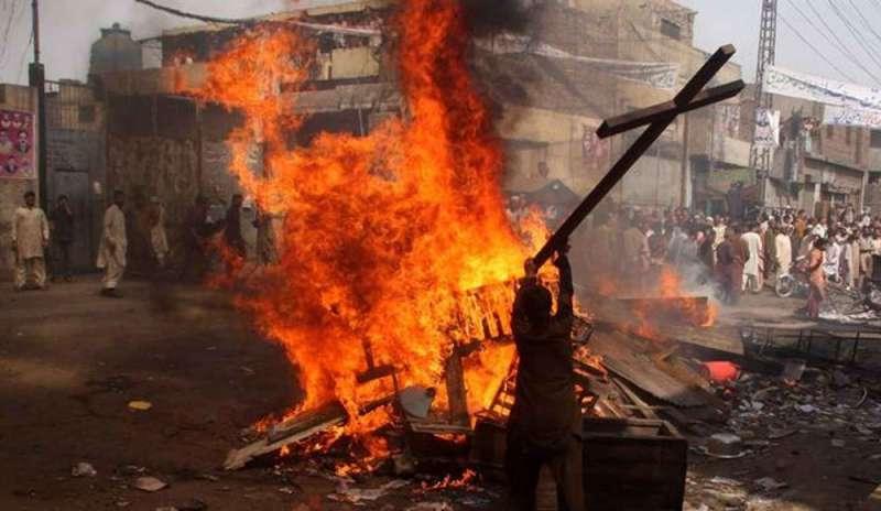La foto ritrae degli uomini mentre bruciano delle croci